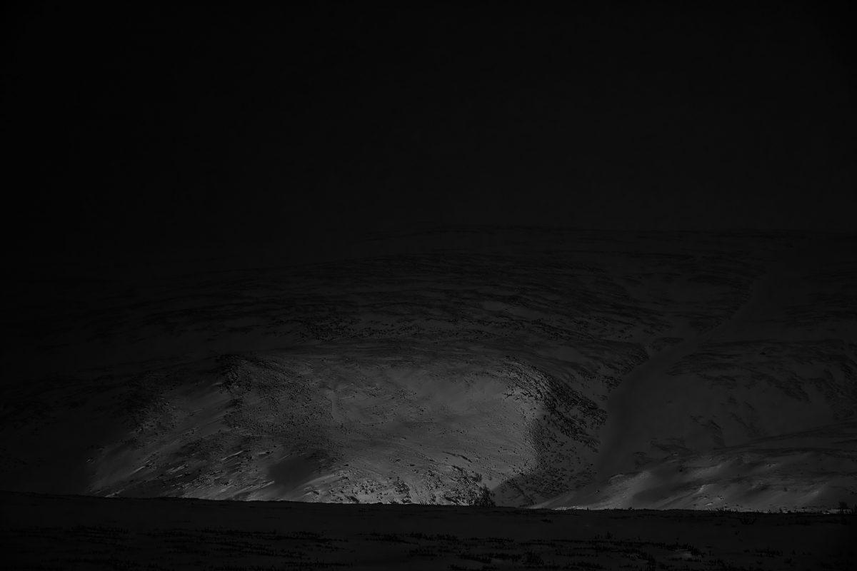 photo en noir et blanc d'un point lumineux dans la neige