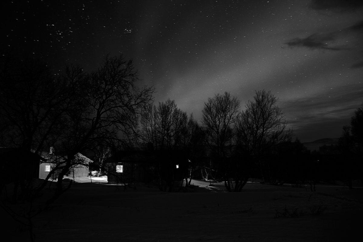 photo en noir et blanc de cabanes norvégiennes sous une aurore boréale